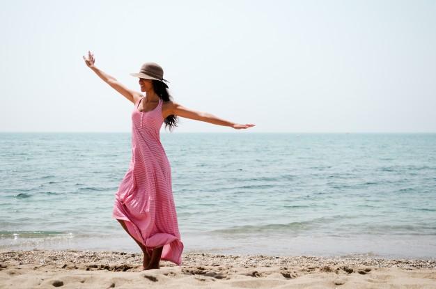 mujer-alegre-bailando-en-la-playa_1139-44